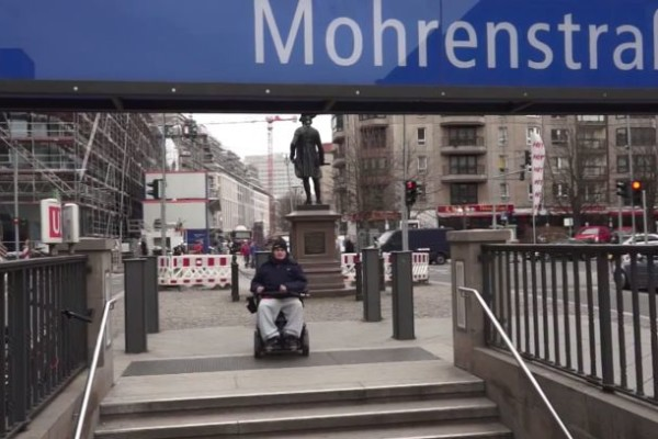 Rollstuhlfahrer vor U-Bahn-Treppe
