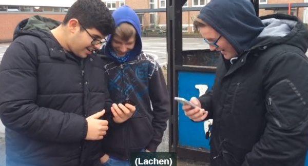 Drei Jugendliche schauen auf ihre Handys und lachen höhnisch