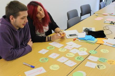 Junge Frau und junger Mann erstellen mit Hilfe von Moderationskarten das Spiel.