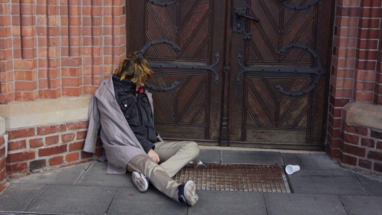 Eine zusammengesunkene Person, in schäbiger Kleidung, deren Gesicht man nicht erkennt, vor einer Kirchentür