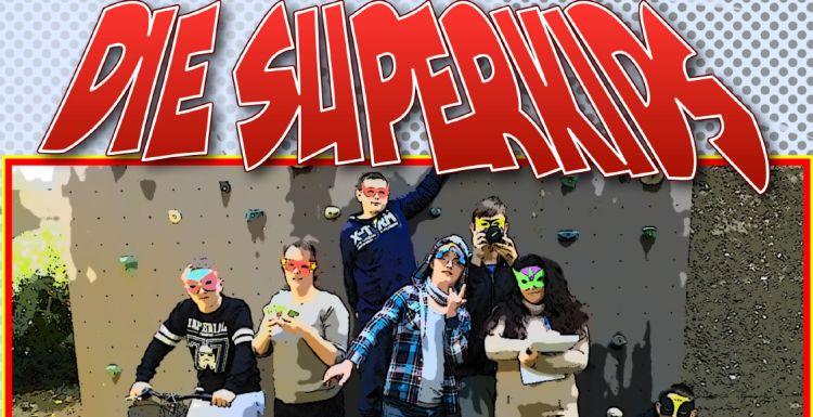 """Jugendliche vor einer Kletterwand, mit Superheldenmasken im Gesicht. Stark comicartig verfremdet. Typische Comic-Schrift: """"Die Superkids"""""""