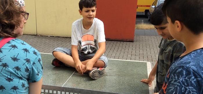 Junge sitzt mit Mädchen auf einer Tischtennisplatte
