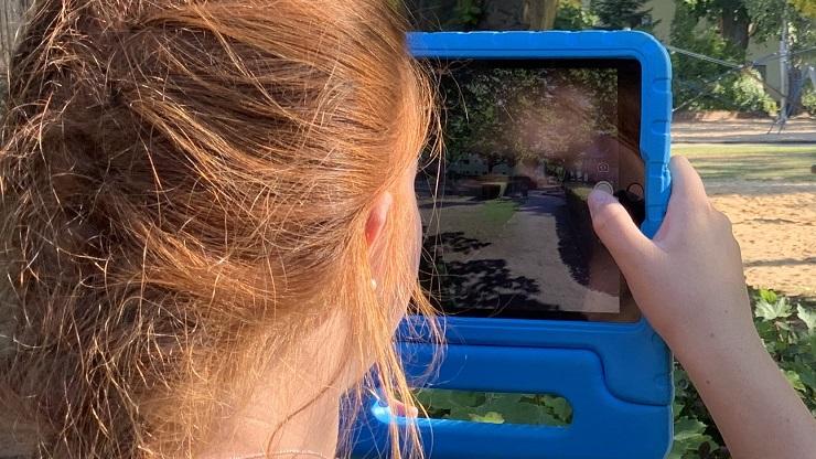 Mädchen fotografiert ihre Umgebung mit iPad